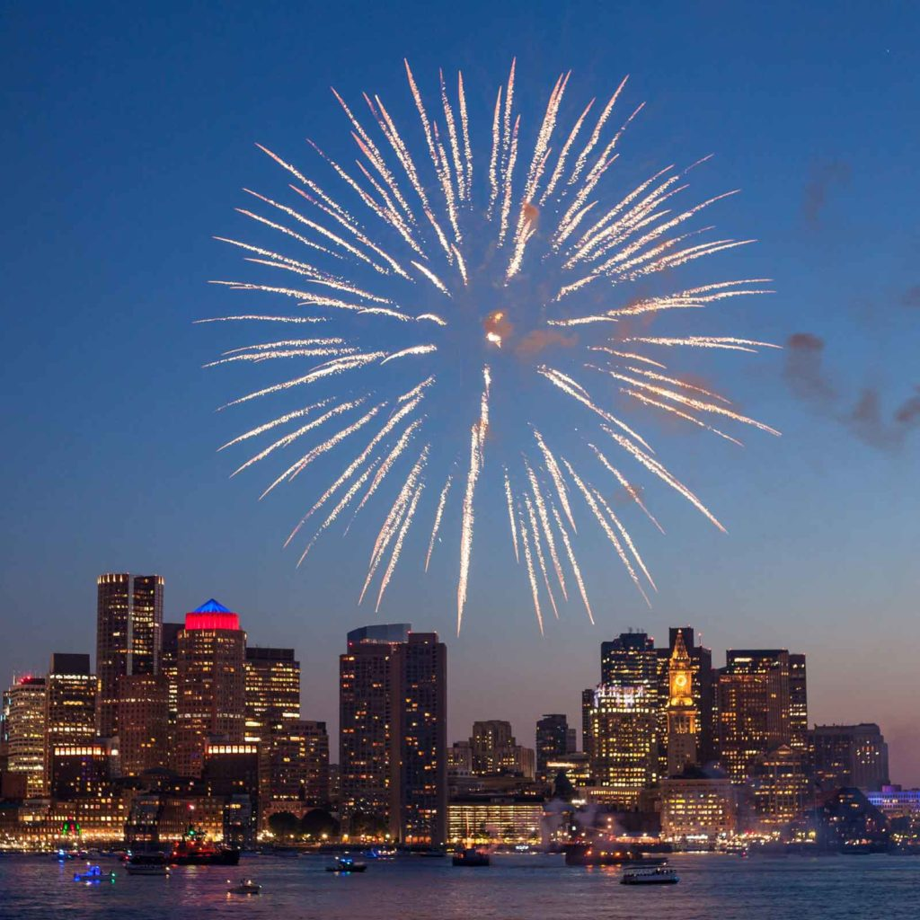 Photo of the Boston skyline from across the Charles River. A massive firework is exploding in the sky.