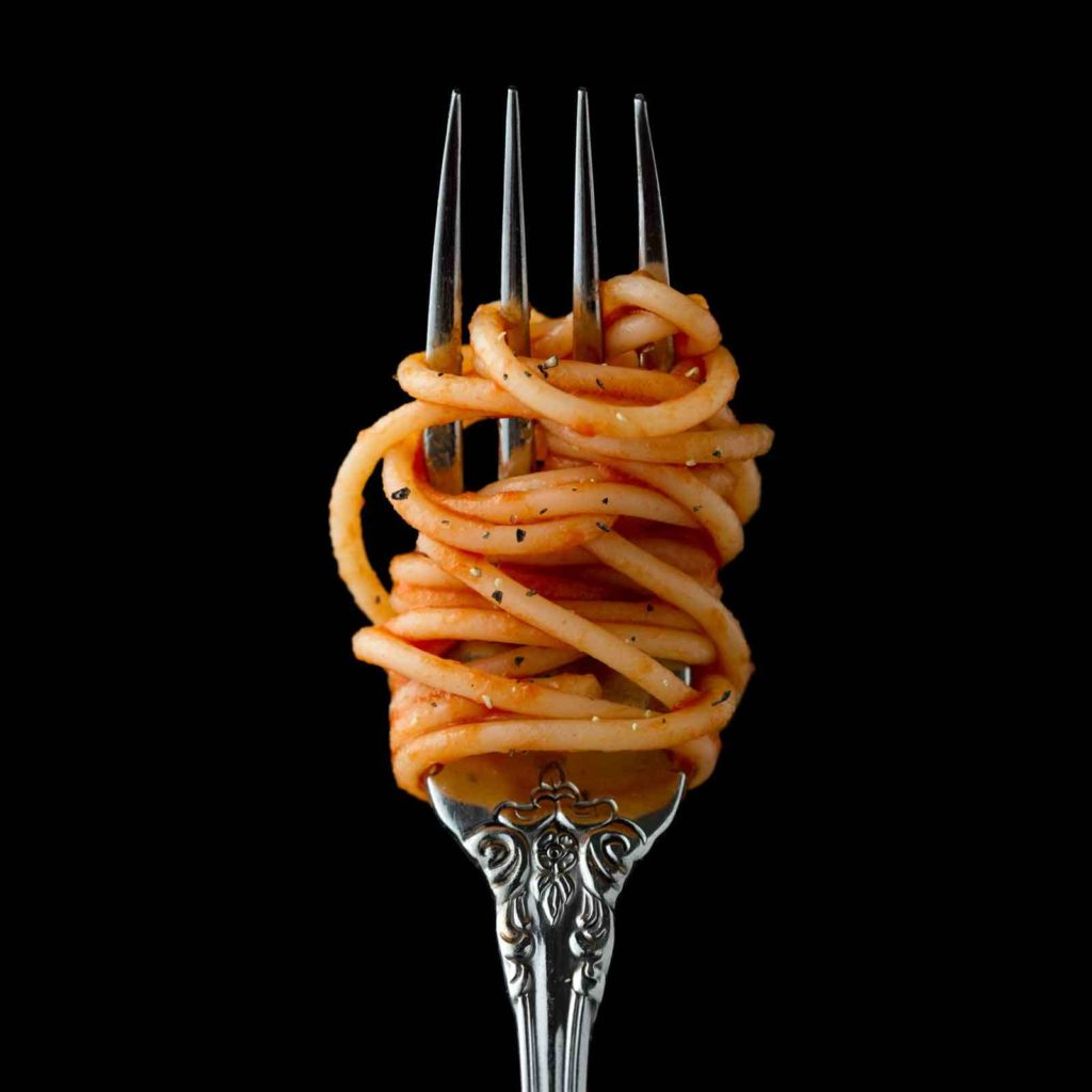 Closeup of a fork with spaghetti twirled around it, held up against a black background.