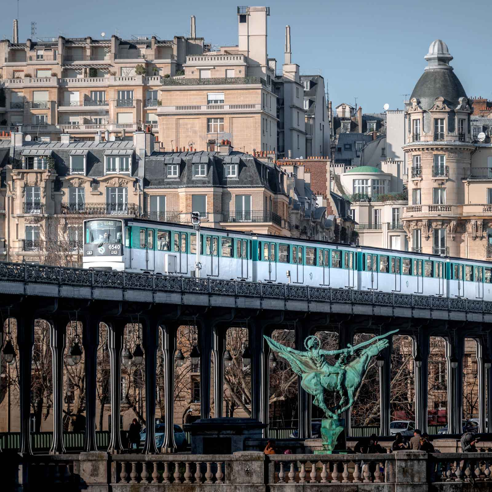 Photo of a Paris train driving by on an overhead train track.