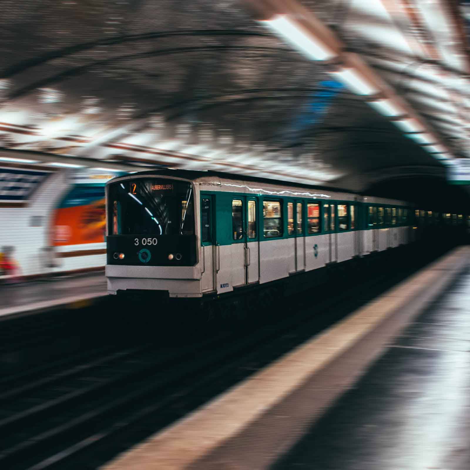 Photo of a Paris Metro train pulling into an underground station.