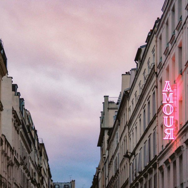"""Photo looking down a street between 2 buildings. On the building to the right, there is a pink neon sign that says """"Amour."""""""