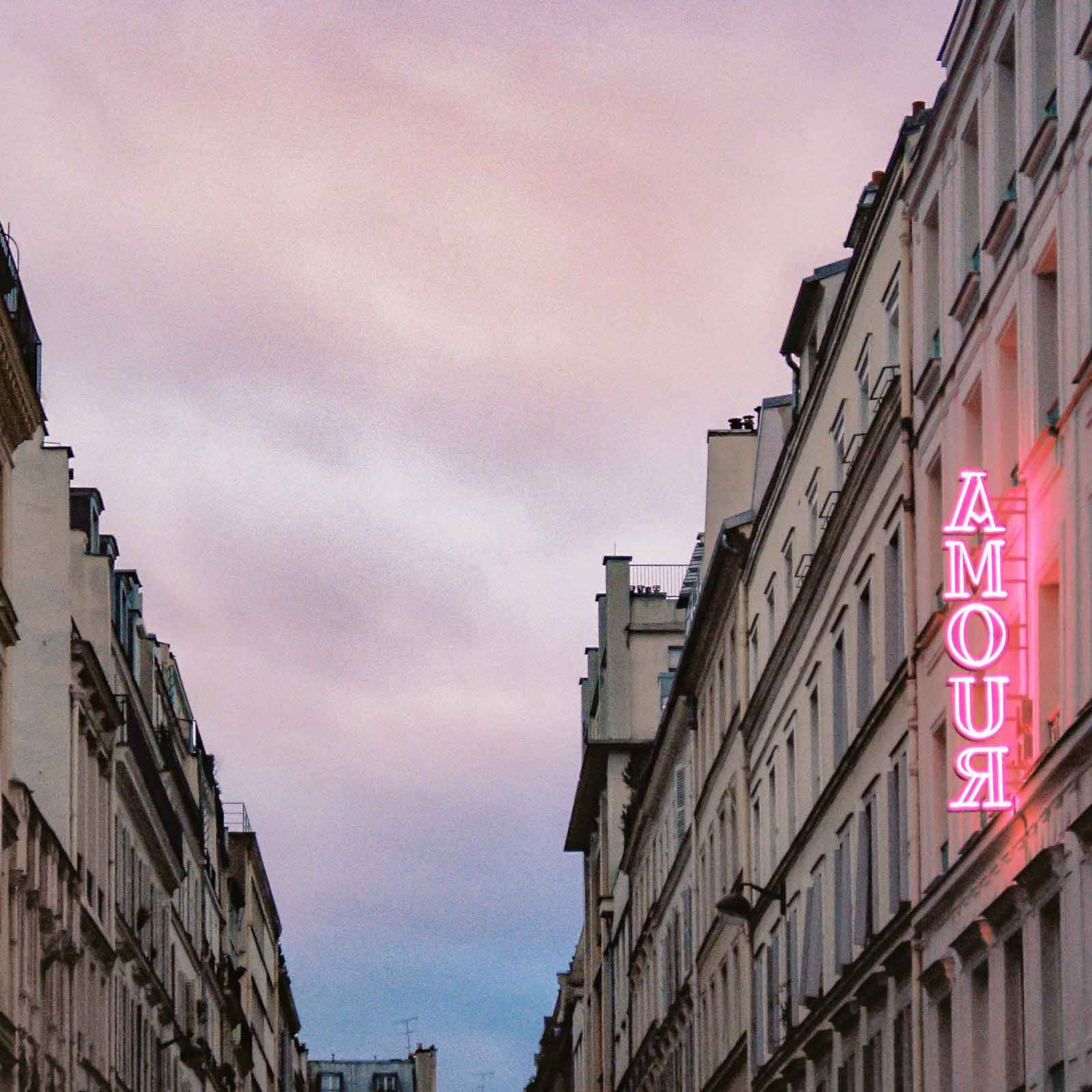 "Photo looking down a street between 2 buildings. On the building to the right, there is a pink neon sign that says ""Amour."""