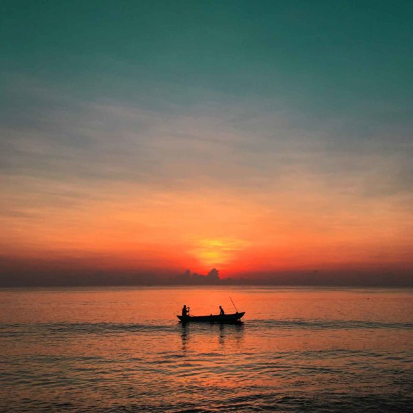Photo of a gorgeous orange and teal sunset with a silhouette of a small boat with 2 people in it.