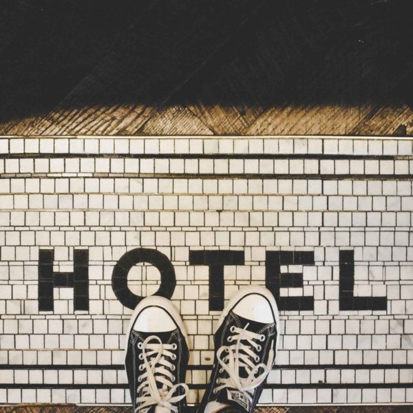 "Top down photo of 2 feet wearing black Converse sneakers. The white tile floor spells out ""Hotel"" using black tile."