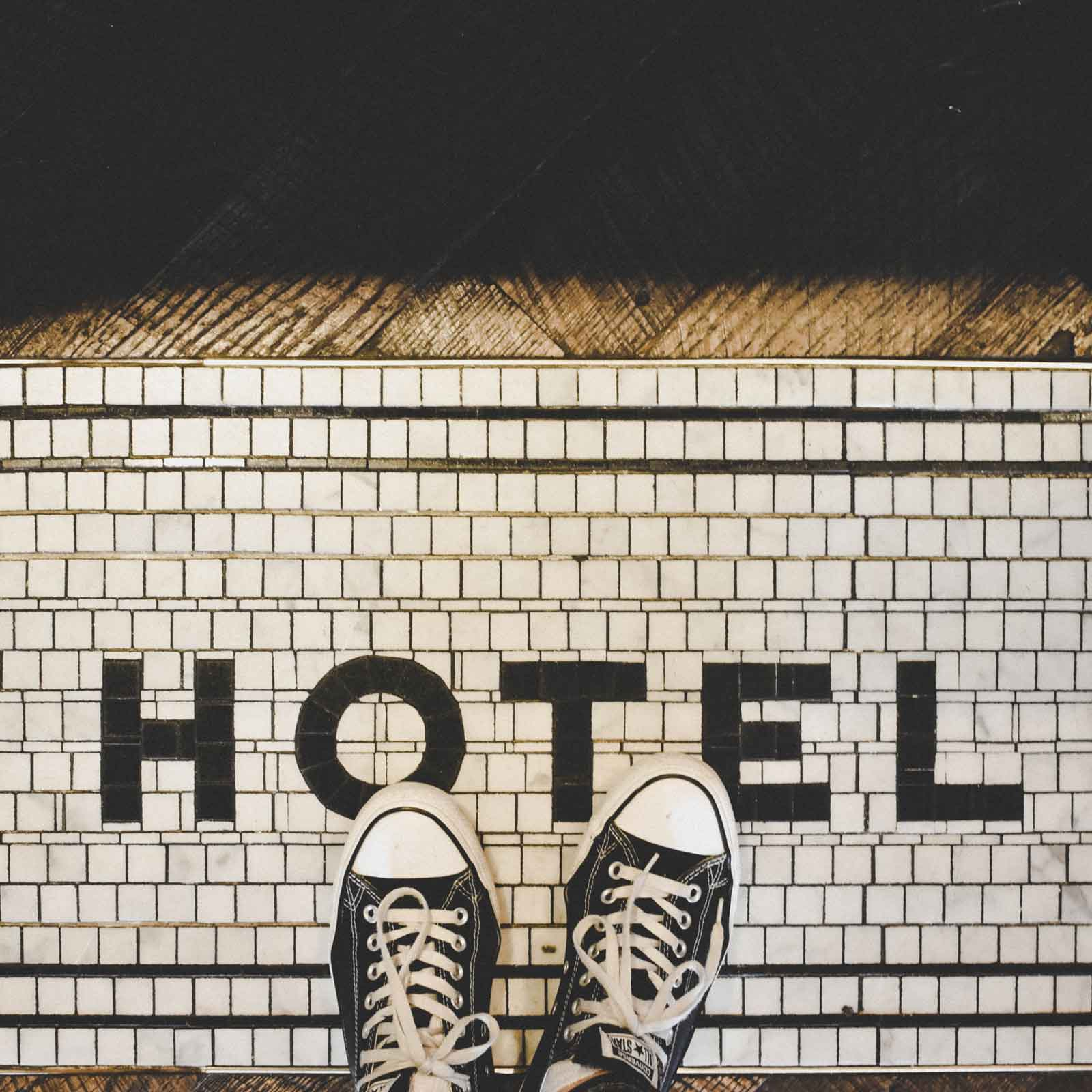 """Top down photo of 2 feet wearing black Converse sneakers. The white tile floor spells out """"Hotel"""" using black tile."""