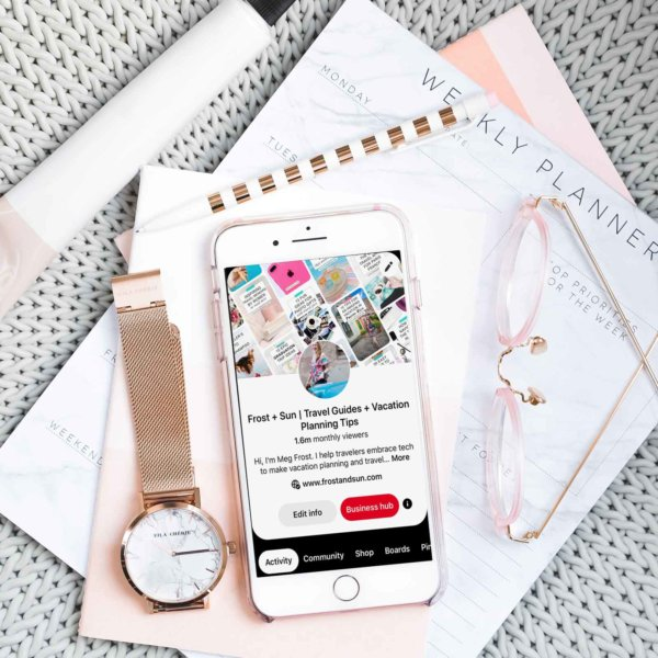 Flat lay photo with gray, pink, and white objects artfully arranged. In the middle is an iPhone open to a Pinterest profile page.