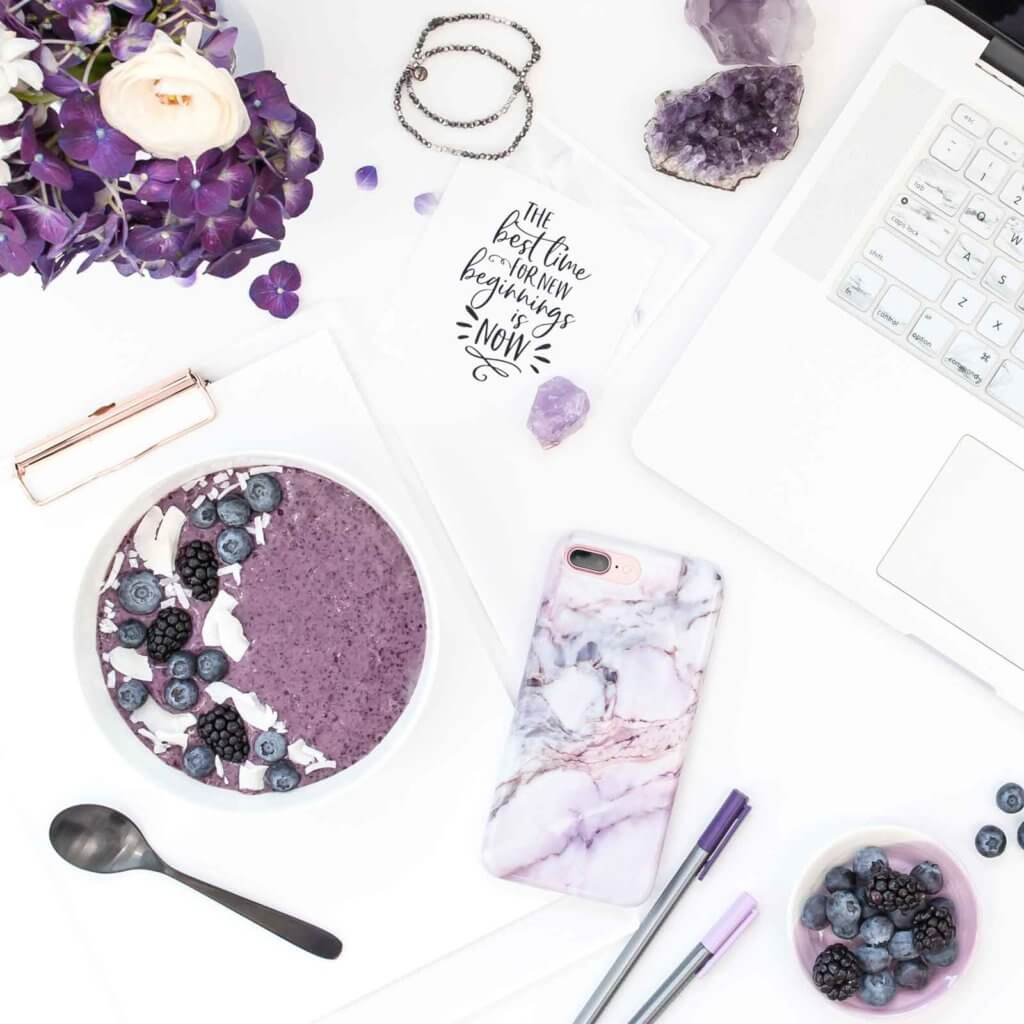 Flat lay photo of a white surface with white and purple objects, such as an amethyst rock, purple flowers, a purple smoothie bowl, a purple marble print phone case, a silver laptop, and purple pens, artfully arranged.