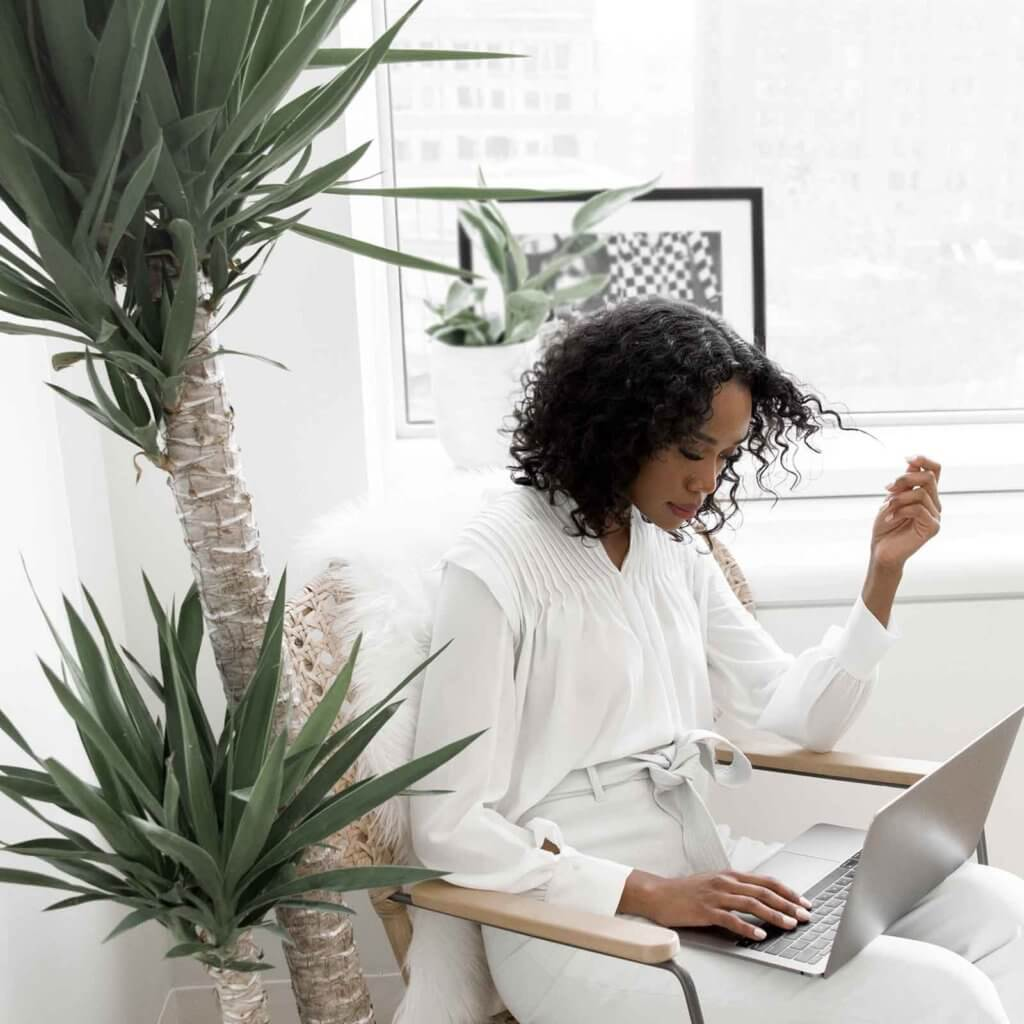 Photo of a woman wearing a white blouse and light grey pants reading something on her laptop while twirling her curly hair with one hand.