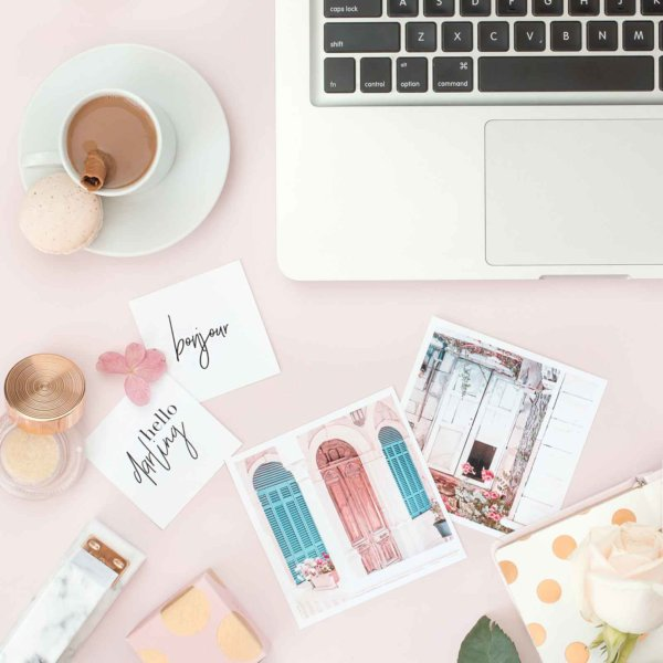 Flat lay photo of a light pink surface with artfully arranged items such as pastel printed photos, a silver laptop, a white rose, and a cup of espresso with a macaron on the side.