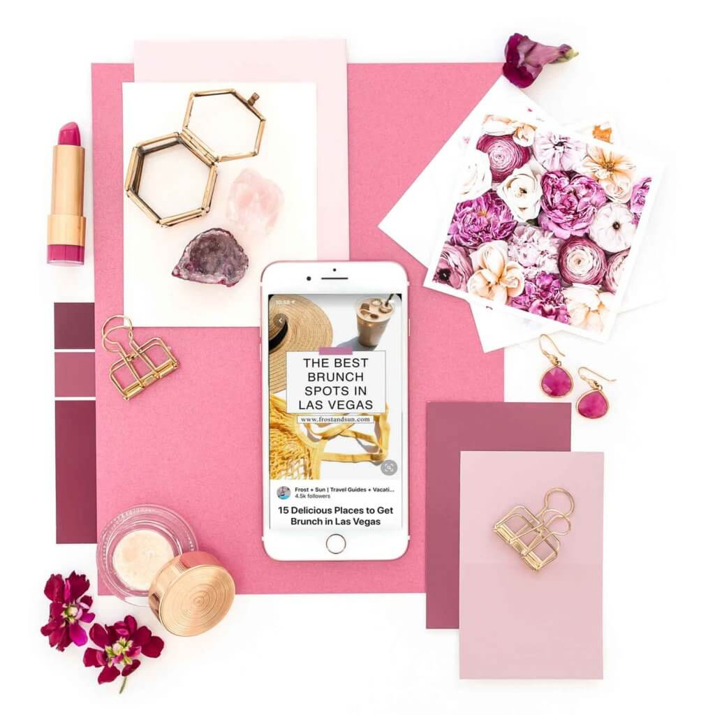 Flat lay of pink and gold objects, such as lipstick, papers, flowers, and makeup, artfully arranged. In the middle is a white iPhone open to a pin on Pinterest with extra data like profile photo, profile name, and blog post title.