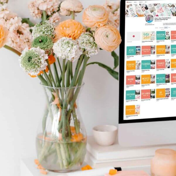 Closeup photo of a white desk with pink and peach office accessories, a clear vase full of pink, peach, and white flowers, and a Mac computer open to a Pinterest profile page.