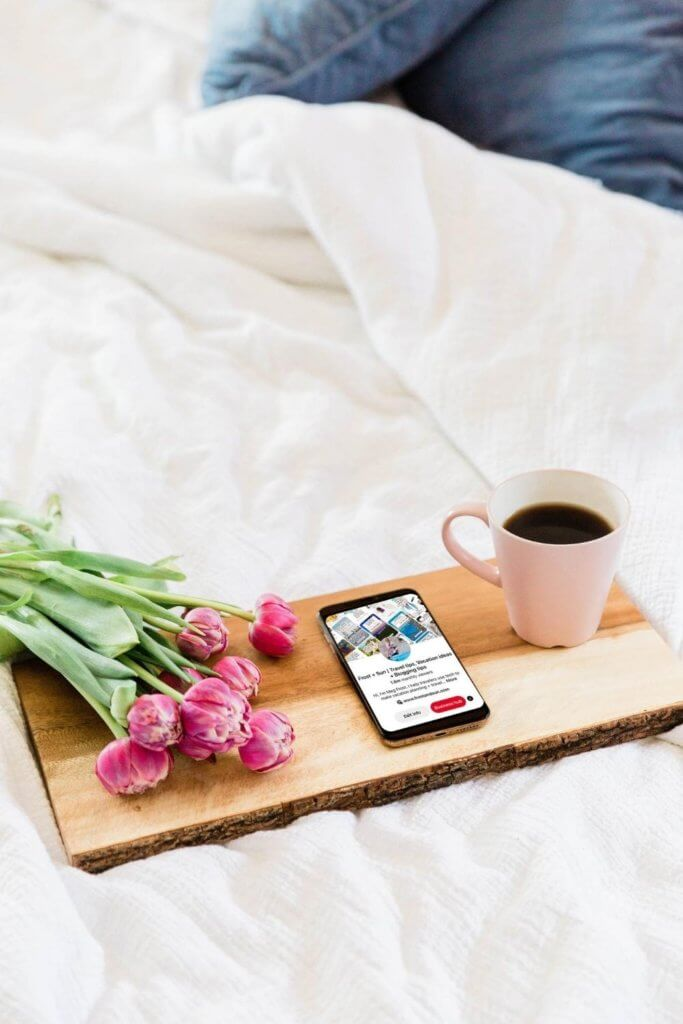 Photo of a wooden tray on an unmade bed. The tray has a bunch of pink flowers, a cup of coffee and a mobile phone open to a website.