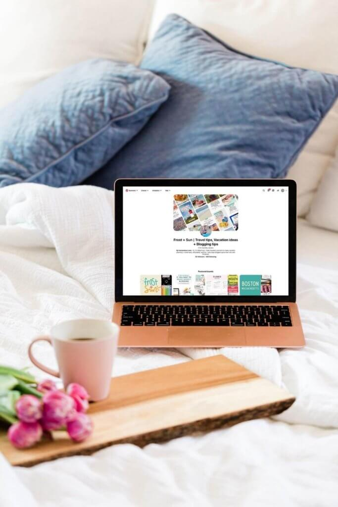 Photo of a laptop open to Pinterest on an unmade bed with white linens. A wooden tray sits nearby with a bunch of pink tulips and a cup of coffee.