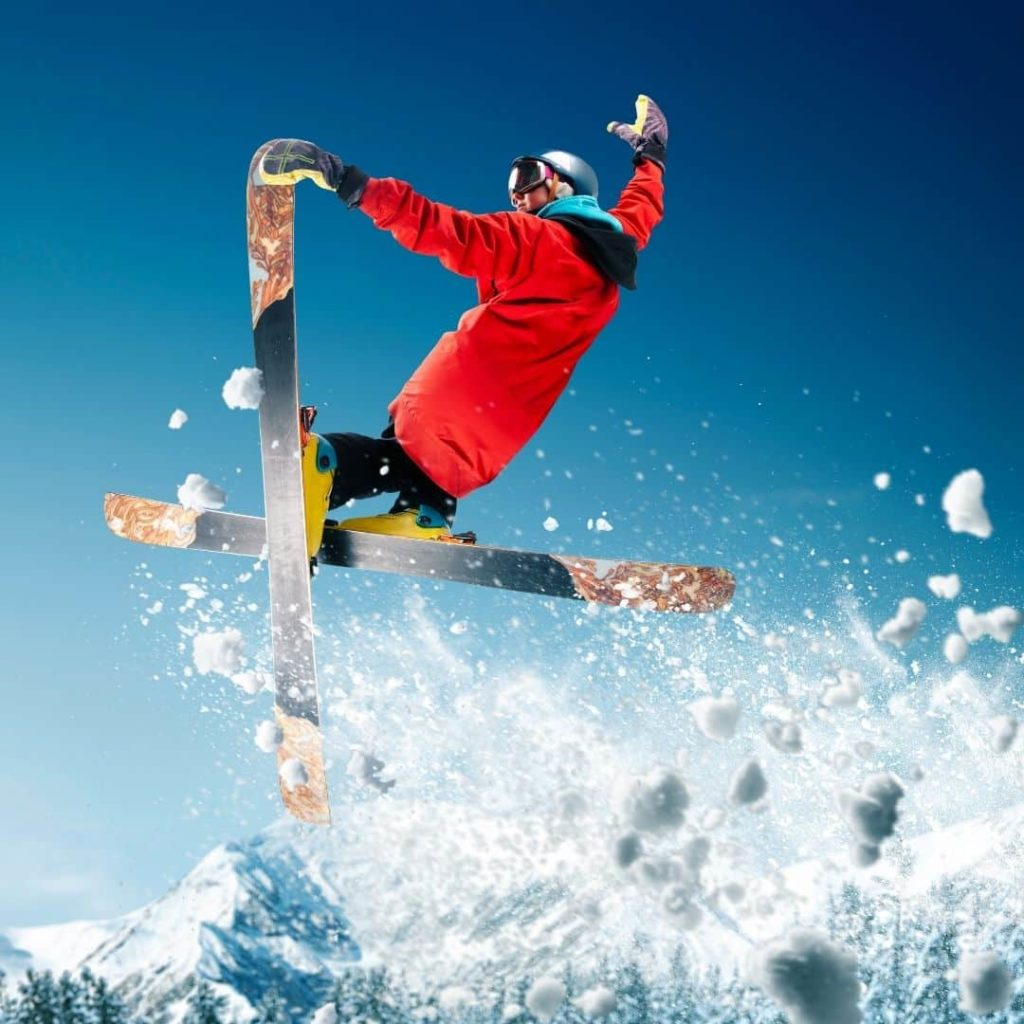 Photo of a person in colorful snow gear on skis mid-air off a ski jump.
