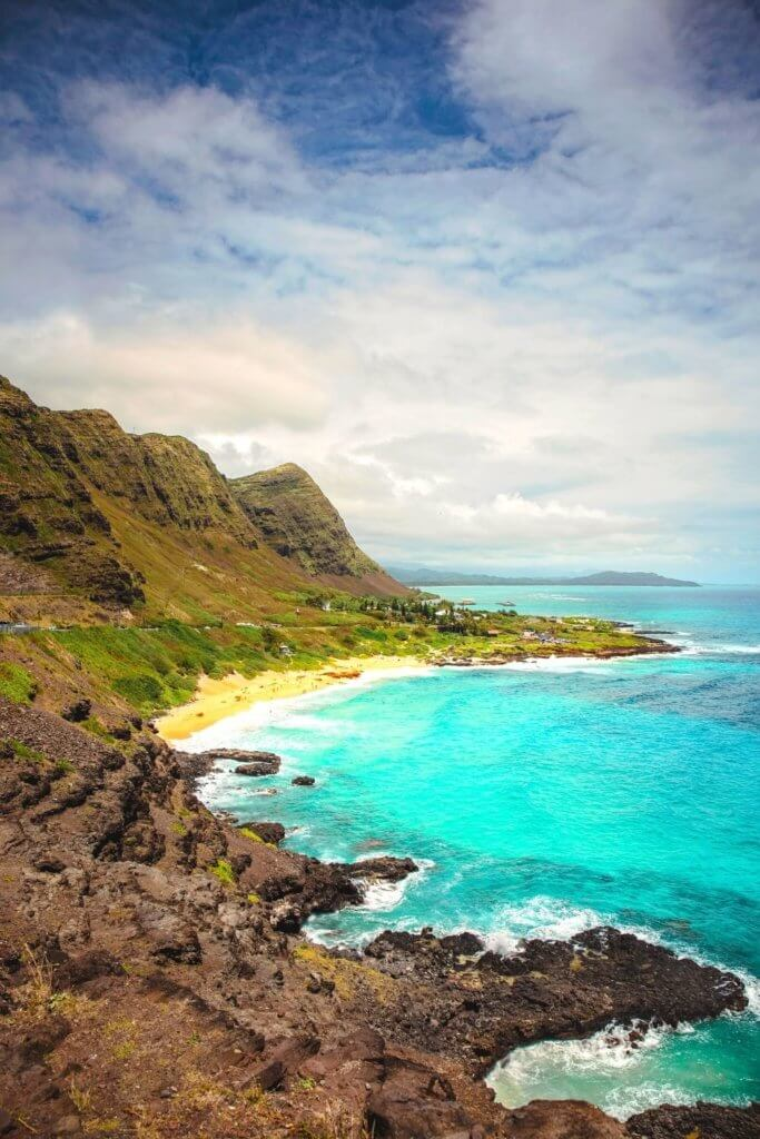 Photo of a coastal landscape in Hawaii with rocky cliffs and turquoise water.