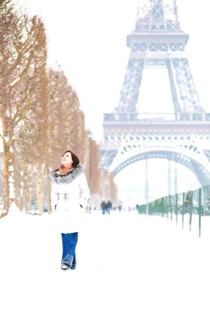 Photo of a woman walking through the snow with the Eiffel Tower in the background.