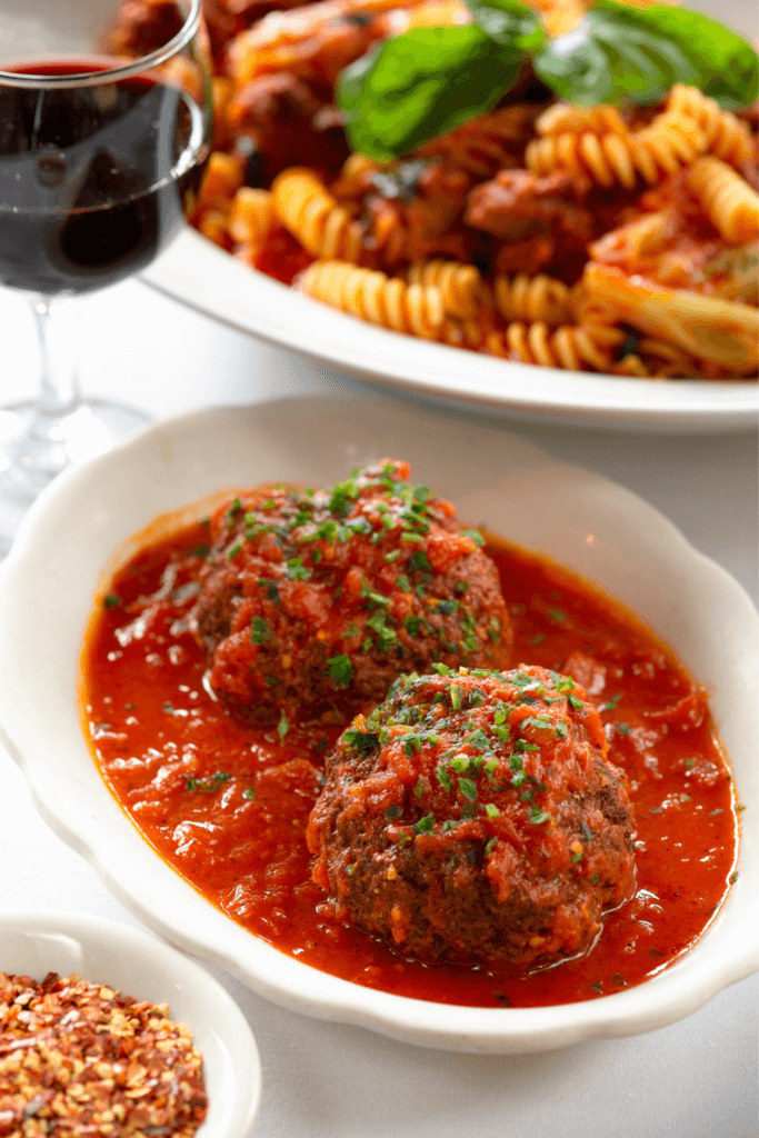 Closeup of 2 giant meatballs in a dish filled with tomato sauce. A bowl of rotini pasta and a glass of red wine in the background.