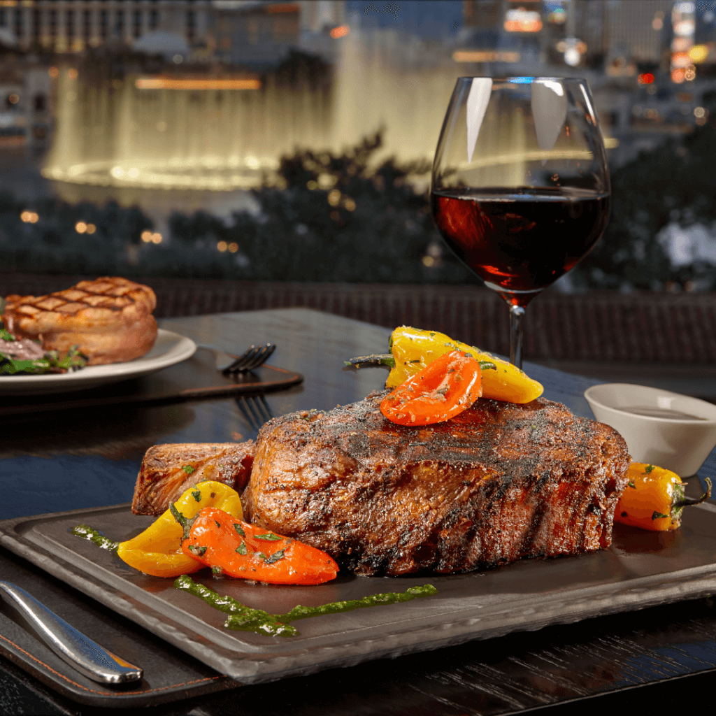 Closeup of a steak dinner with a glass of red wine with the Bellagio Vegas fountains in the background.