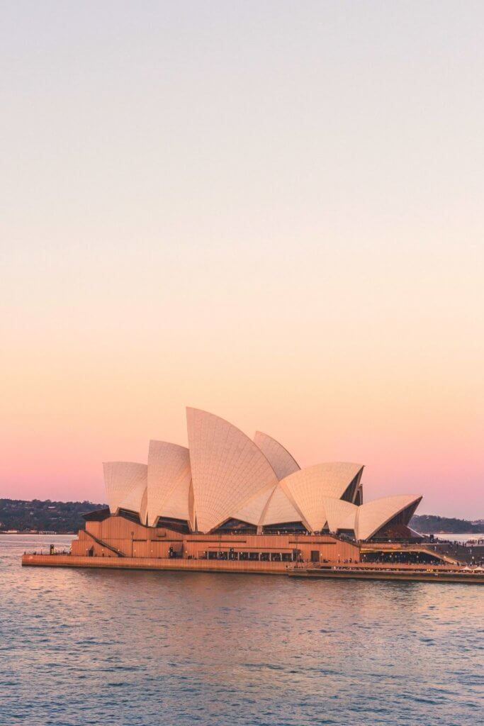 Photo of the Sydney Opera House set against a pink and yellow pastel sky.