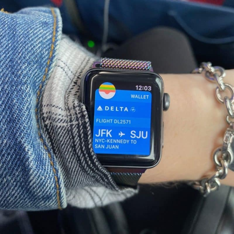 Closeup of a woman wearing a smart watch with a Delta boarding pass open on the screen.