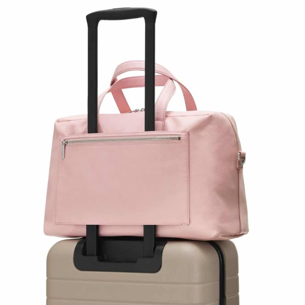 Closeup of a hardshell carry on suitcase with a tote bag slid over the luggage handle.
