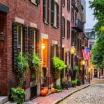 Landscape view of a cobblestone alley with brick townhomes in Beacon Hill, Boston.