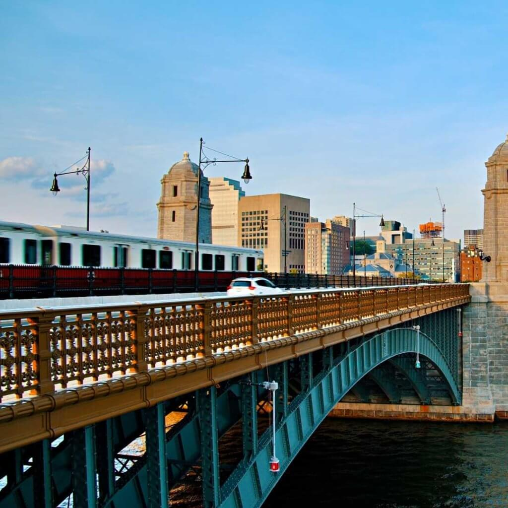 Photo of a bridge over the Charles River in Boston with cars and a Red Line train crossing over it.