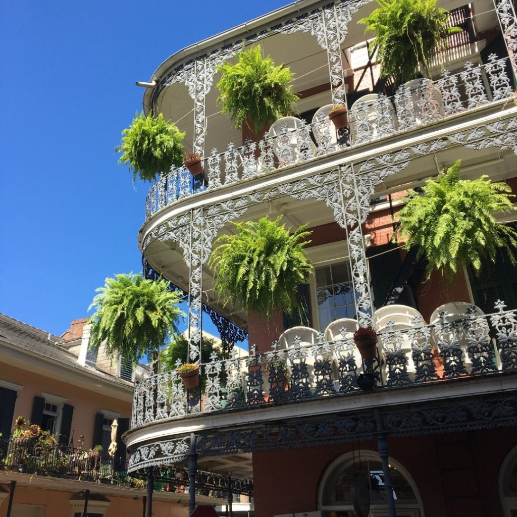 Closeup of a brick building in New Orleans with iron balconies and hanging plants.