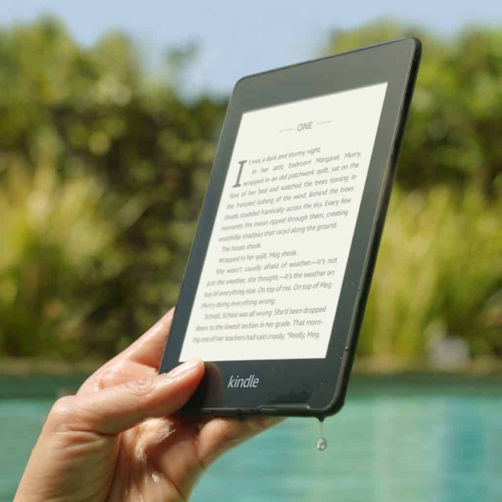Closeup of a person holding up a Kindle Paperwhite reader with a pool in the background.