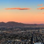 Panoramic aerial view of the sprawling metro Las Vegas area with mountains and sunset in the background.