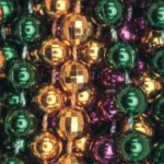 Closeup of green, gold, and purple Mardi Gras beads.