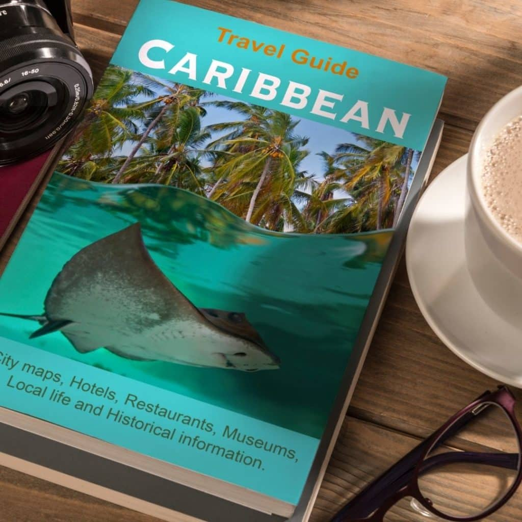 Closeup of a travel guide to the Caribbean on a wooden table.