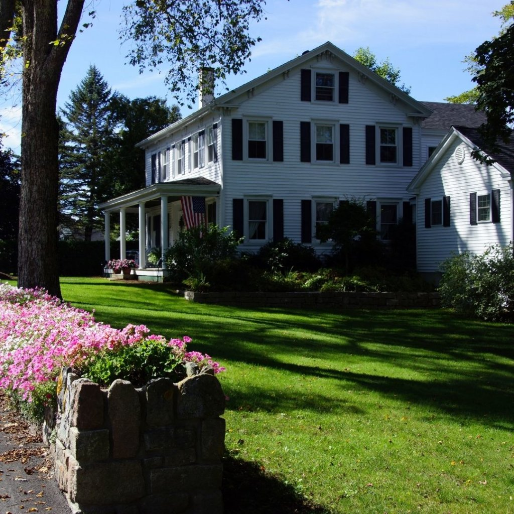 Photo of a white cottage in Bar Harbor with pink flowers blooming outside.
