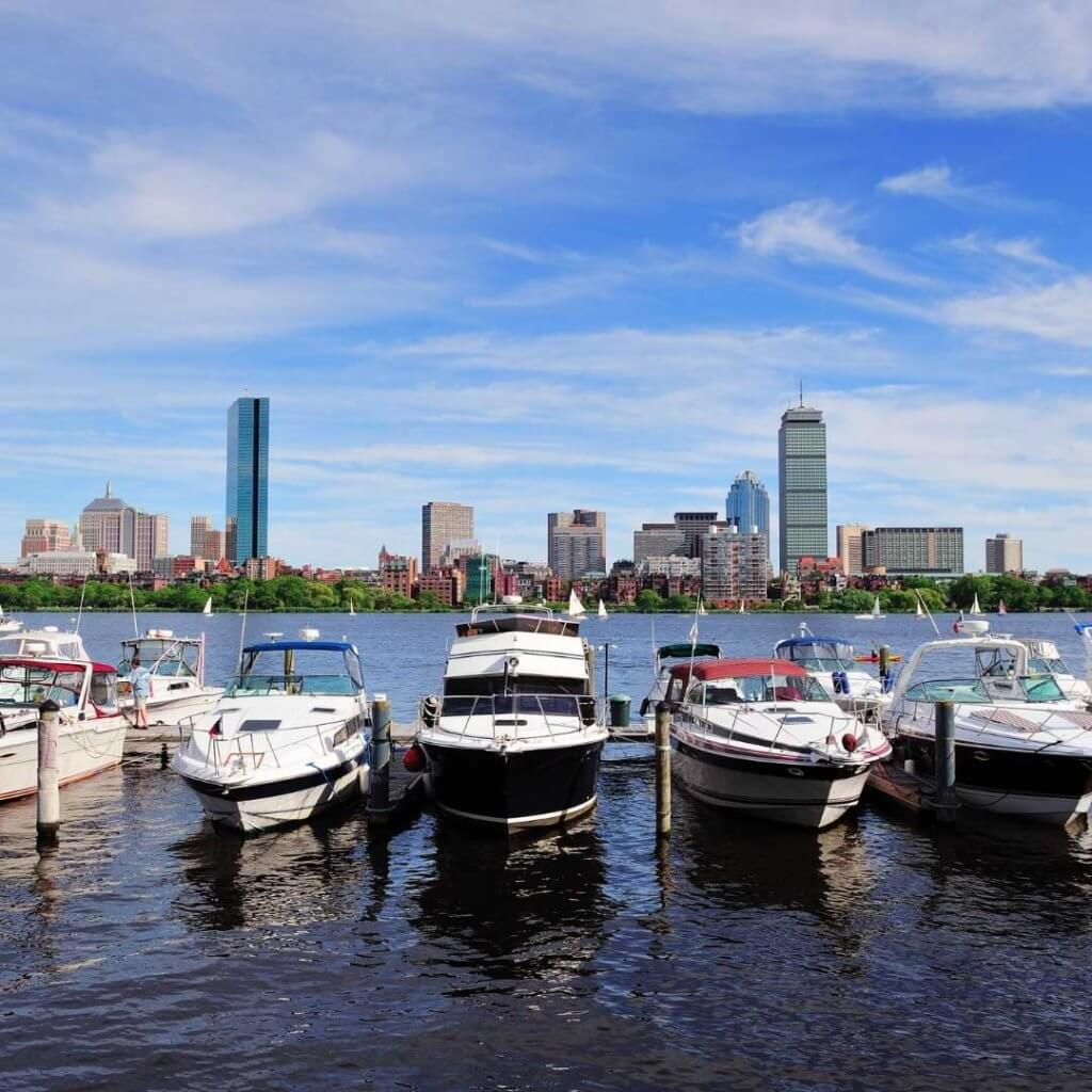 Photo of boats docked along the shore of the Charles River in Boston.