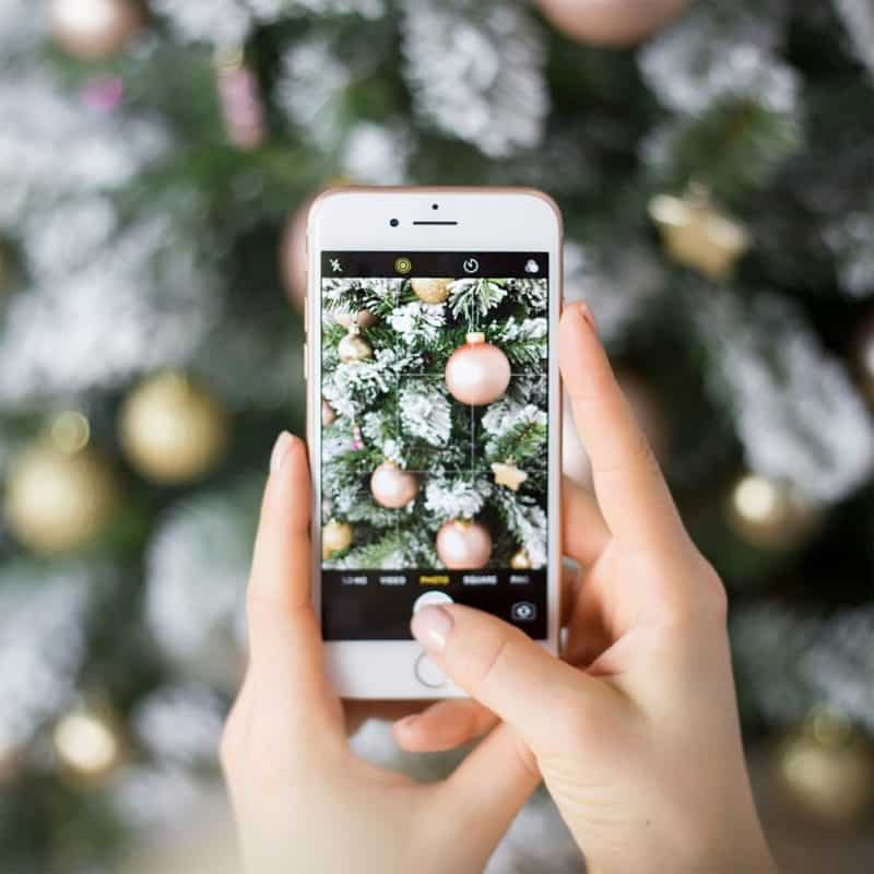 Closeup of a person taking a photo of a Christmas tree with an iPhone.