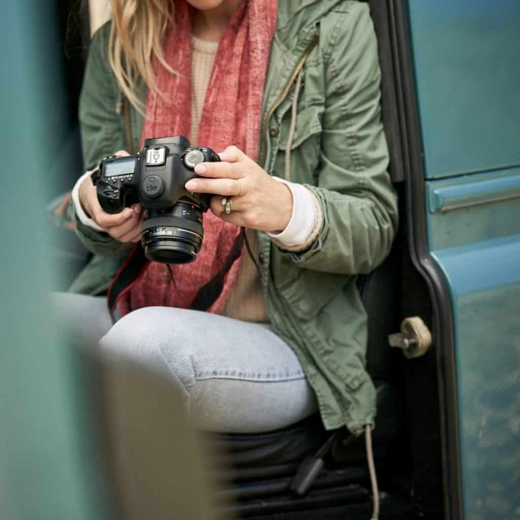 Closeup of a woman holding a professional camera with a Tile Sticker on it.