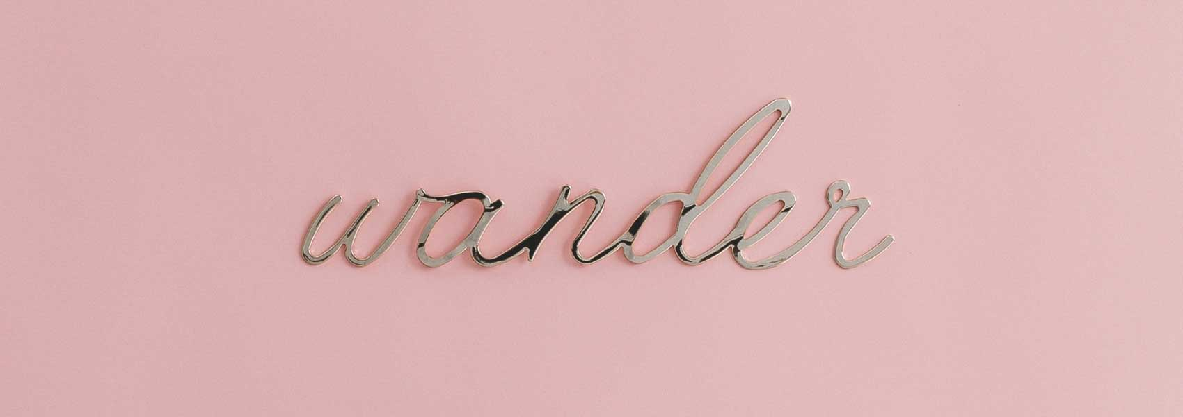 """Pink background with a shiny silver metal sign that says """"wander."""""""