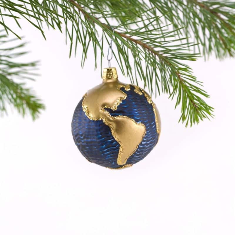 Closeup of a globe Christmas ornament hanging from an evergreen tree.