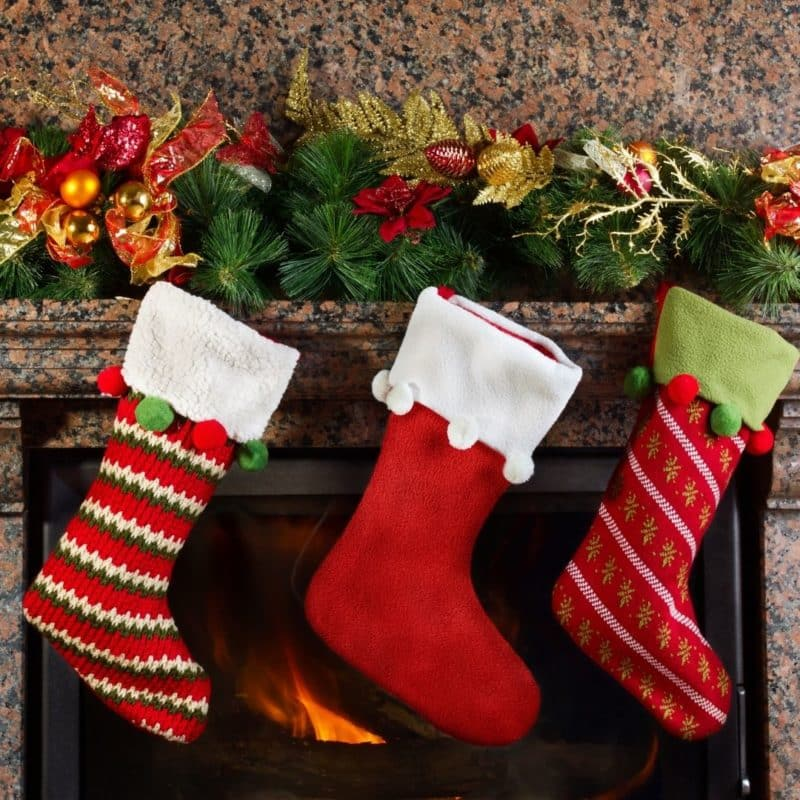 Closeup of a fireplace with an evergreen bough on the mantle and 3 Christmas stockings hanging.