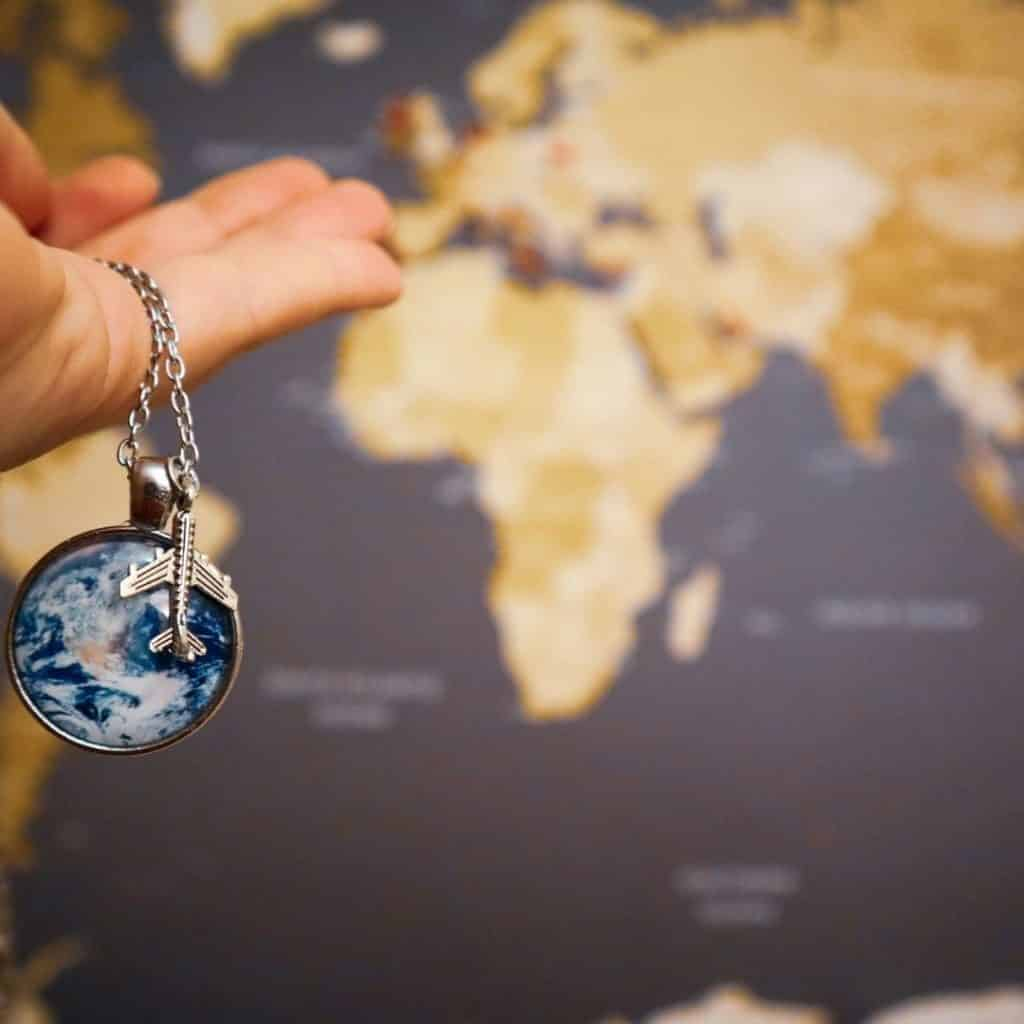 Closeup of a person holding a silver necklace chain with a silver plane charm and a globe-like charm.