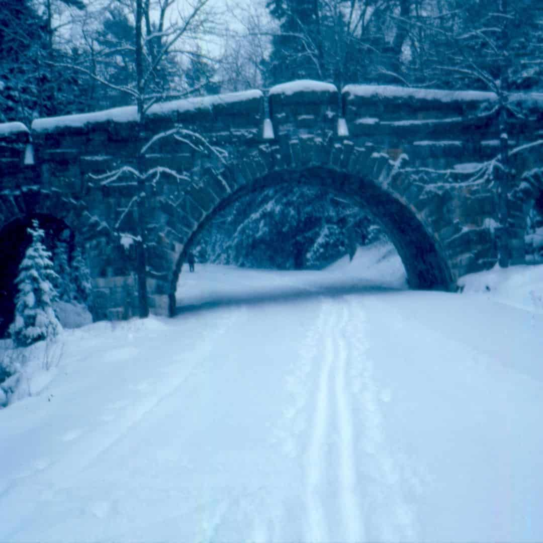 Photo of a stone bridge and carriage road in Acadia National Park covered in snow.