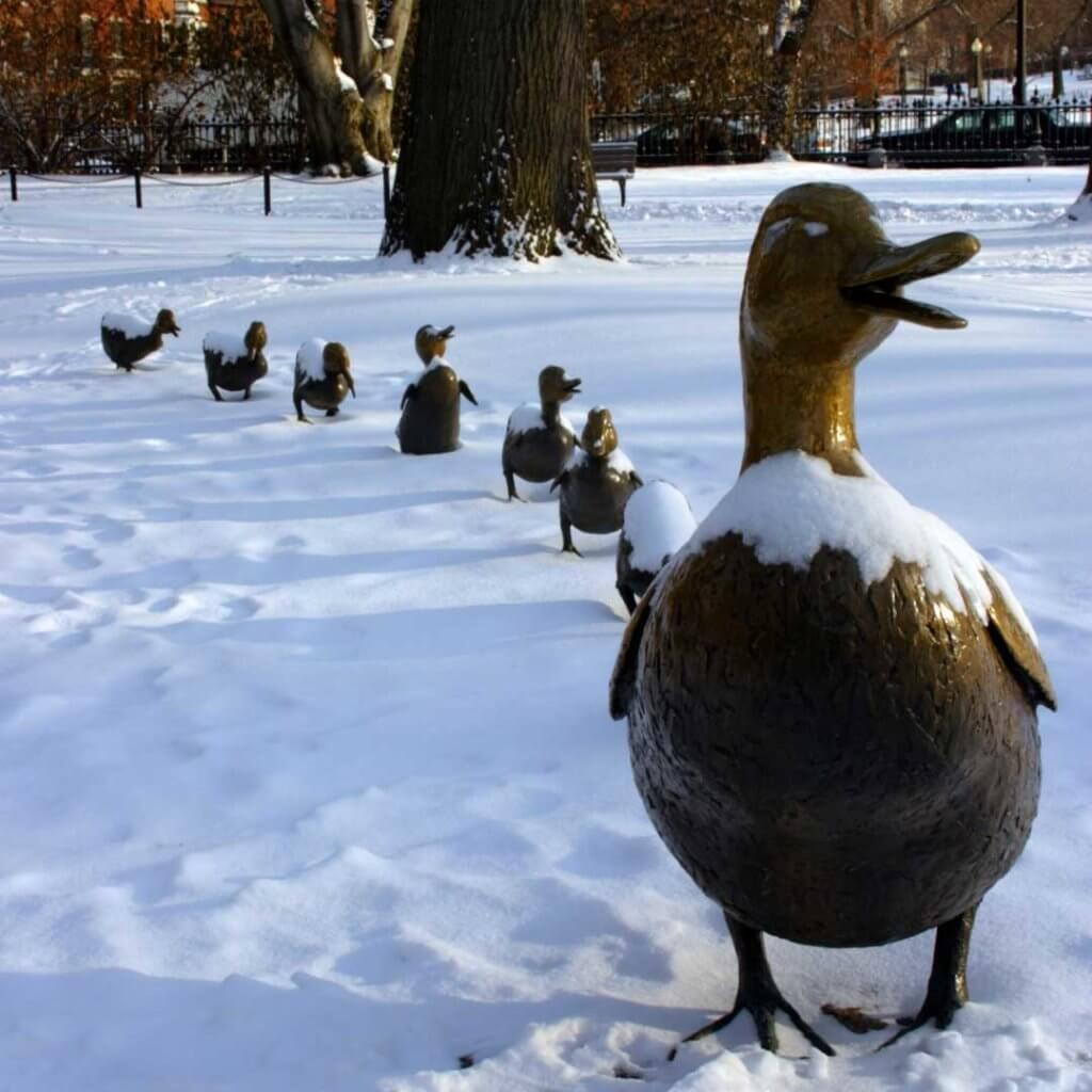 Photo of the Make Way for Ducklings statue in the Boston Public Garden, covered in snow.