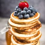 Closeup of a tall stack of thick pancakes with blueberries, a big strawberry, and maple syrup on top.