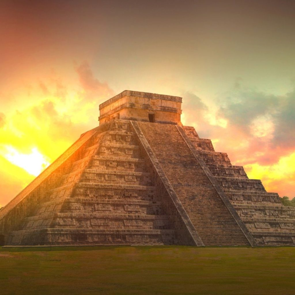 Photo of Chichen Itza in Mexico with the sun rising in the back.