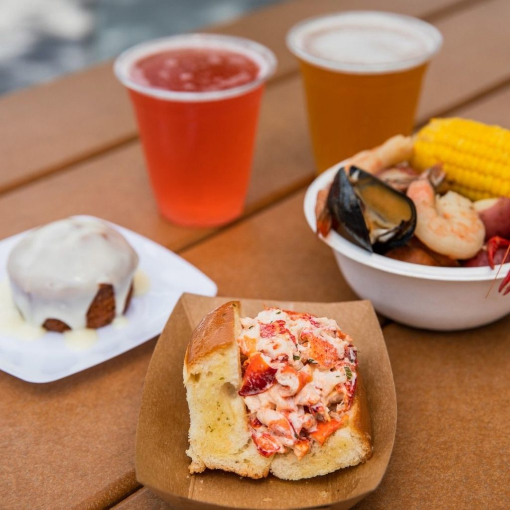 Closeup of 2 beers, a lobster roll, and a small bowl of food from a traditional New England clambake.