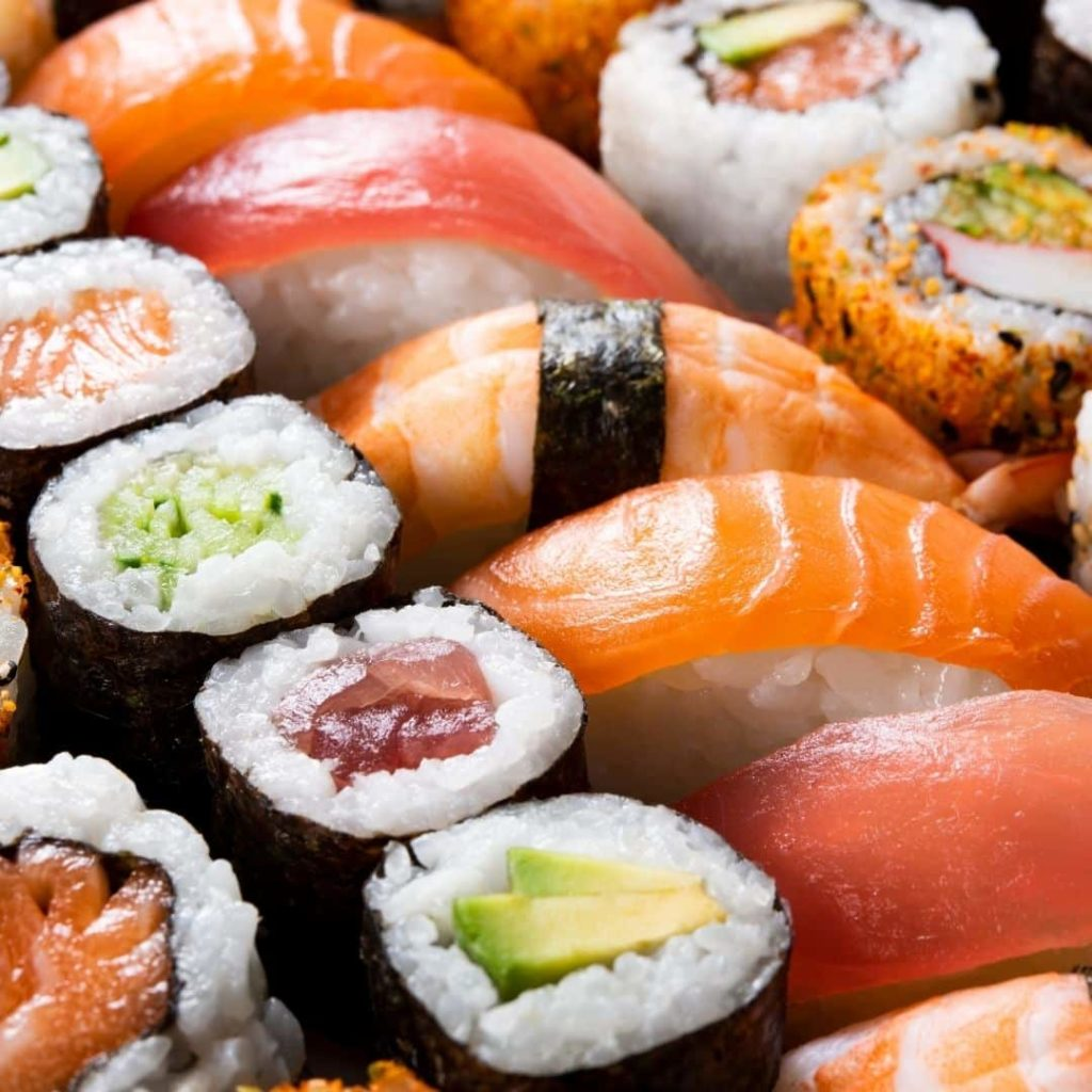 Closeup of a colorful platter of sushi and sashimi with lots of orange, salmon, and green colors.