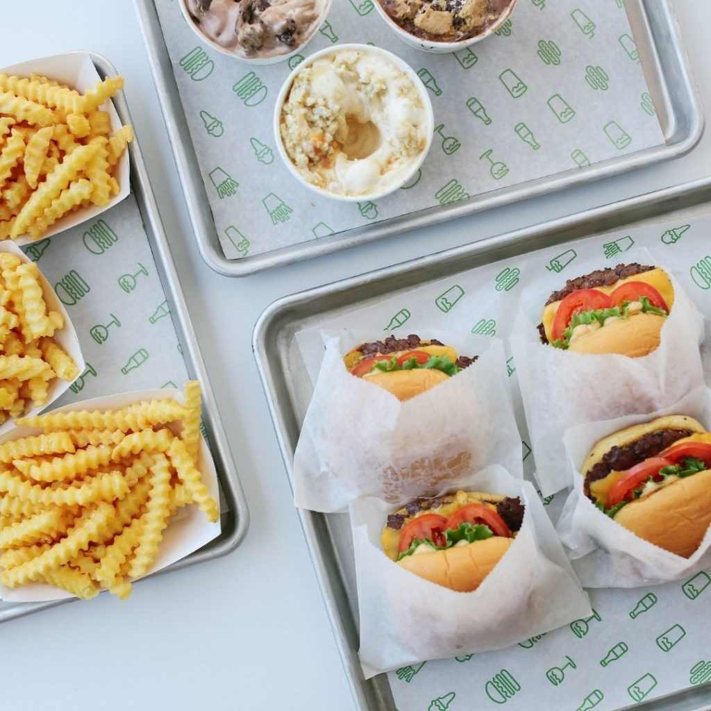 Flat lay photo of 3 dining trays from Shake Shack, one with crinkle french fries, one with milkshakes, and one with cheeseburgers.