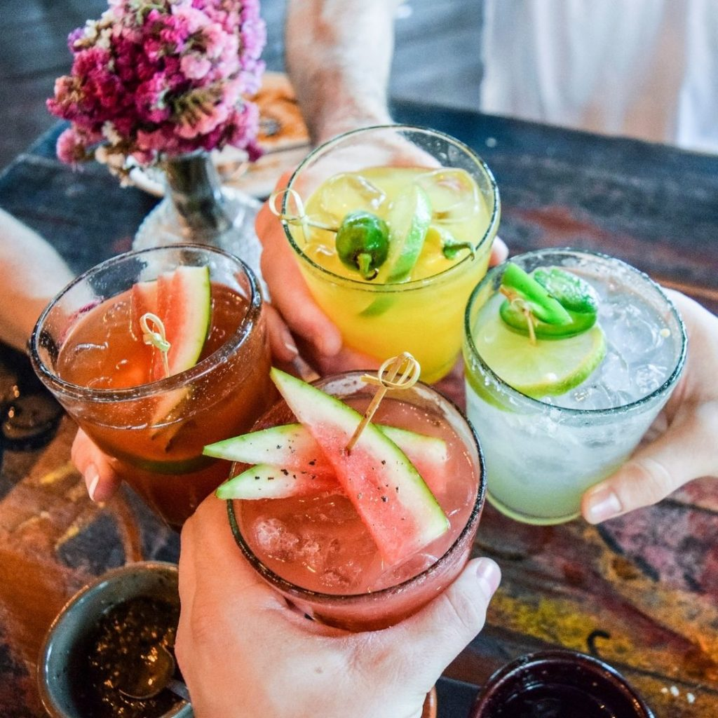 Closeup of 4 people holding colorful margarita cocktails.