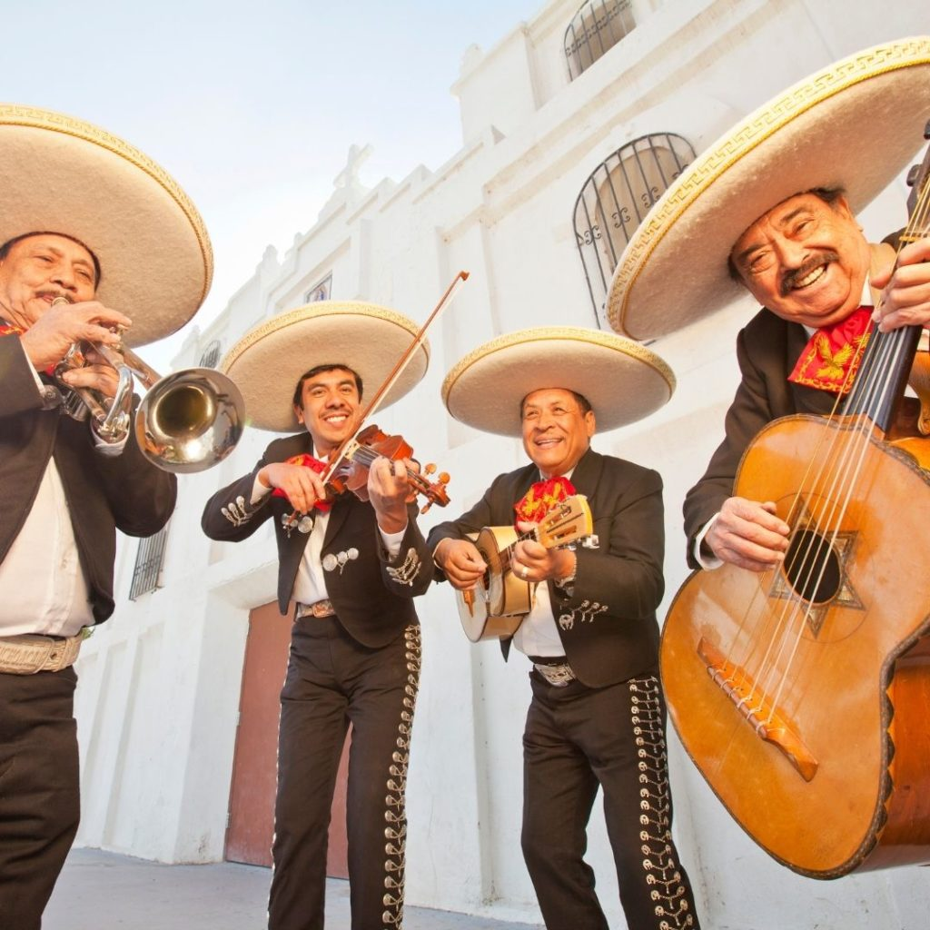Photo of 4 men dressed in traditional Mariachi costumes, playin instruments.