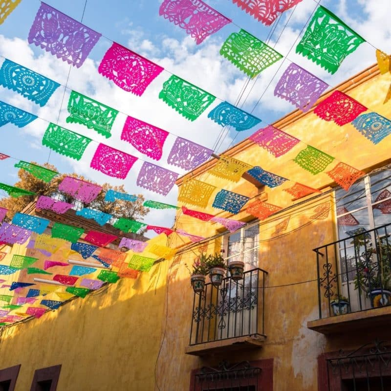 Photo of a yellow building with colorful flags strung up over the street.